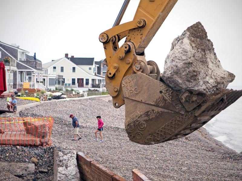Scituate residents walk along the shore just south of Egypt Beach in Scituate as workers replace the aging seawall. Recent studies estimate that the sea level could rise in New England by 2 to 7 feet by the end of the century – a result of climate change