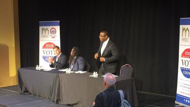 Boston City Councilor Tito Jackson (R, standing) joins Mayor Marty Walsh (L) and moderator Adrian Walker on stage for Boston's first mayoral debate.