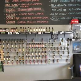Bottles of e-liquid lining the walls of Eastern Vapor with chalk board listing flavors behind.