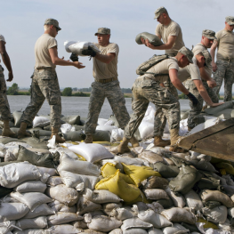 National Guardsmen stack sand bags along the Missouri River to contain flooding.
