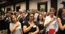 A packed crowd recited the Pledge of Allegiance before a hearing on prohibiting local law enforcement from collaborating with immigration enforcement Friday at the State House.