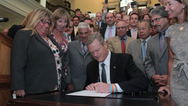 Gov. Charlie Baker signs a bill to modernize how municipal governments interact with the state at a bill signing Tuesday.