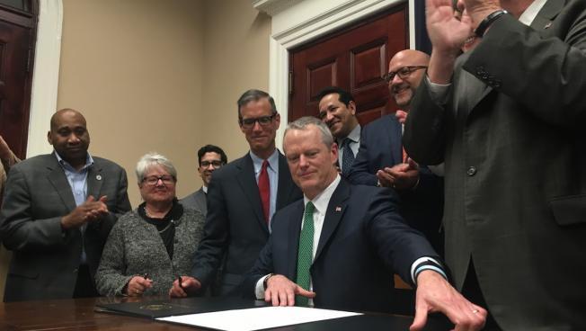 Gov. Baker, surrounded by legislators, signs the criminal justice bill.