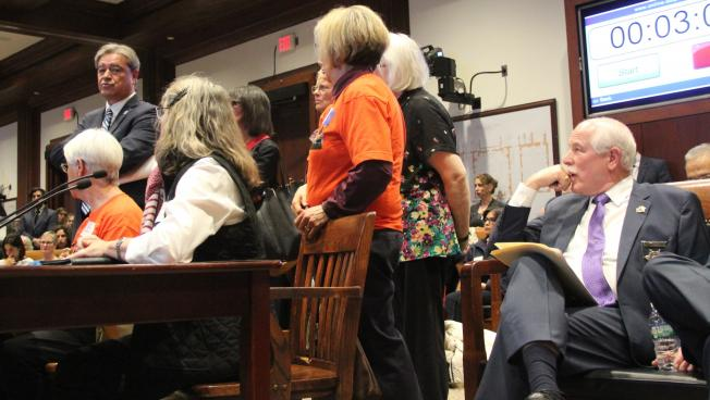Rep. Antonio Cabral (left,) surrounded by immigration activists, testifies about his bills to stop sheriffs from spending state money on immigration law enforcement and sending prisoners out of state for labor. Bristol County Sheriff Tom Hodgson (right,)