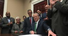 Gov. Baker, surrounded by legislators, signs the criminal justice bill.